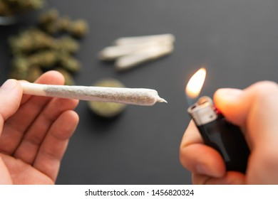 joint with weed in hand and lighter, Cannabis buds on black table, close up, grinder with fresh marijuana,