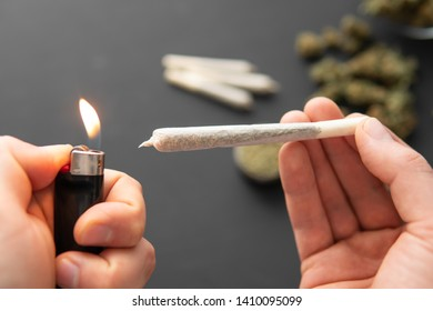 joint with weed in hand and lighter, close up, grinder with fresh marijuana, Cannabis buds on black table,