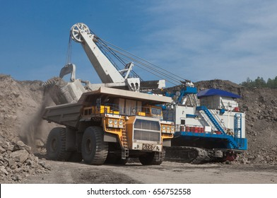 The joint work of the excavator and dump truck. Quarry.