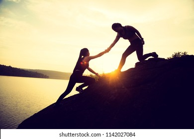 The joint work teamwork of two people girl sport  help each other on top of a mountain climbing team
