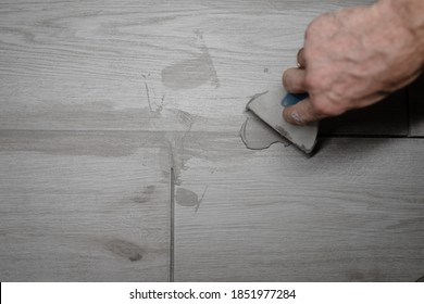 jointing of floor tiles. Grouting tiles seams with a rubber trowel. Grouting ceramic tiles. Tilers filling the space between tiles using a rubber trowel.