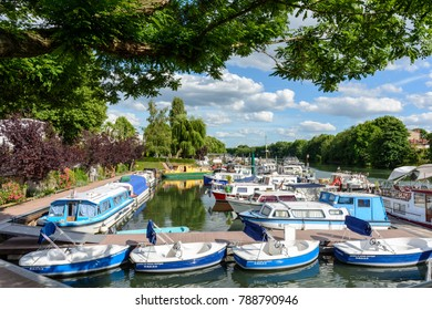 "Joinville-le-Pont, France - June 6, 2017: Riverboats, houseboats and electric rental boats mooring in the marina of Joinville-le-Pont near Paris. The text on the boats says ""Electric boats hire""."