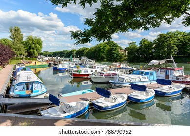 """Joinville-le-Pont, France - June 6, 2017: Riverboats, houseboats and electric rental boats mooring in the marina of Joinville-le-Pont near Paris. The text on the boats says """"Electric boats hire""""."""