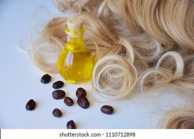 Jojoba oil in a glass bottle, jojoba seeds and healthy, curly, golden blonde color woman's hair on a white background.