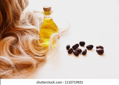 jojoba oil and jojoba seeds on a white background, near light golden blonde hair.