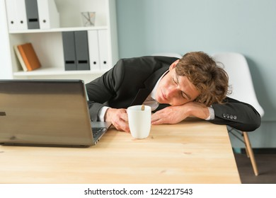 Joke, business people and humor concept - Tired businessman sleeping after hard working day in office interior. Man lying on table with laptop computer on.
