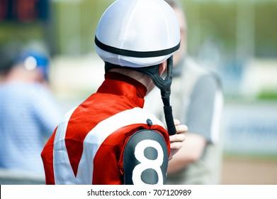 jokey in a helmet from back side