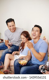 Joking and laughing group of friends eating snacks and drinking wine at party