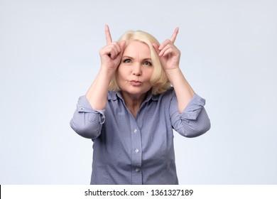 joking senior blonde woman making horns. Studio shot