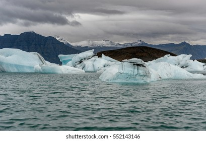 Jokulsarlon Glacier Lagoon in Iceland and Mountain in Background. Blurry Water in Foreground and Dark Cloudy Sky.