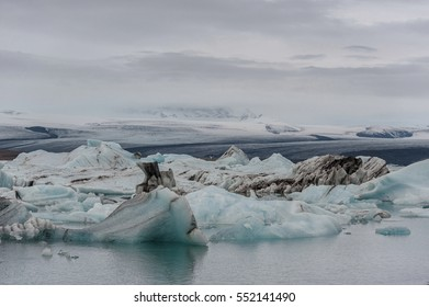 Jokulsarlon Glacier Lagoon and Mountain in Background. Clooudy Sky and Icebergs.