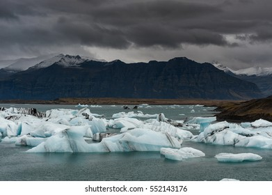 Jokulsarlon Glacier Lagoon and Mountain in Background. Dark Stormy Sky in Background.