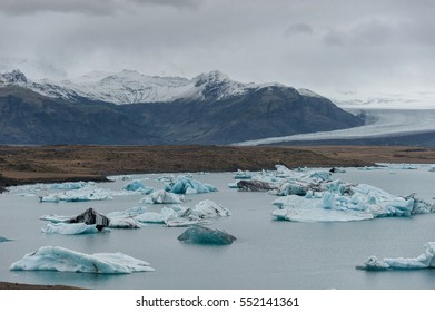 Jokulsarlon Glacier Lagoon and Snowy Mountain in Background. Peaces of Ice in Water.