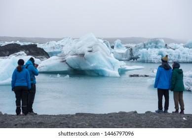 JOKULSARLON, ICELAND - MAY 22, 2019: Tourists admiring and photographing the melting icebergs in the Jokulsarlon glacial lagoon