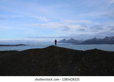 Jokulsarlon, Iceland on 28.02.2019: Woman standing in front of the impressive ice floes at Jokulsarlon glacier lagoon in Southern Iceland