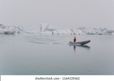 JOKULSARLON LAGOON, ICELAND - September 3th, 2017: The person stood on the rubber boat was working for Jokulsarlon Lagoon boat tour. He excluded the icebergs that block the boat travel way.