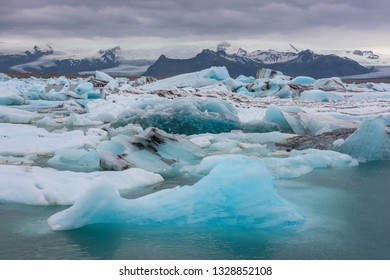 The Jokulsarlon is a large glacial lake in southeast Iceland, the floating ice floes on a quiet surface of gracial lagoon, a dramatic sunset sky is reflected on the surface