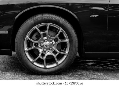 JOLIET, IL, USA - APRIL 7, 2019: The wheel well of a blue 2017 Dodge Challenger GT AWD, which features a 305 horsepower engine. Black and white.