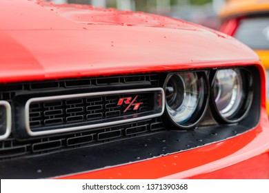 JOLIET, IL, USA - APRIL 7, 2019: The front of a Go Mango colored 2018 Dodge Challenger R/T Scat Pack, which features 485 horsepower with its 6.4L engine.