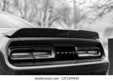 JOLIET, IL, USA - APRIL 7, 2019: The read end of an Octane Red 2018 Dodge Challenger SXT Plus, which features a 305 horsepower HEMI engine. Black and white.