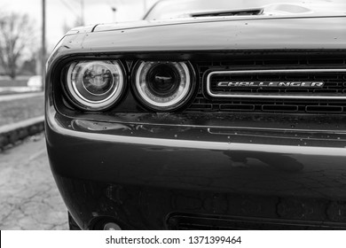 JOLIET, IL, USA - APRIL 7, 2019: The front end of an Octane Red 2018 Dodge Challenger SXT Plus, which features a 305 horsepower HEMI engine. Black and white.