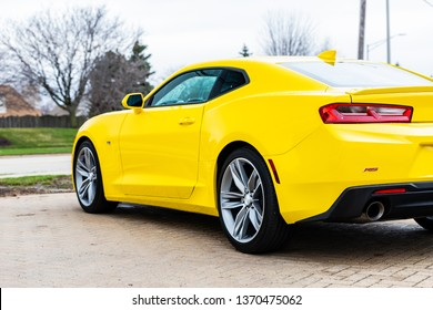 JOLIET, IL, USA - APRIL 9, 2019:  The side and rear of a yellow 2018 Chevrolet Camaro, the models horsepower range from 275 to 650 hp.