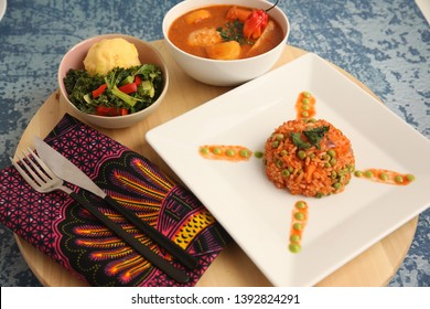 Jollof Rice on White Plate with Ugali and Salad Together with Chicken Stew