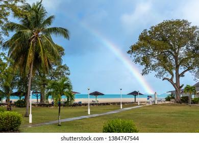 Jolly Beach / Antigua - 04 14 2018: View from Starfish Jolly Beach Resort of Jolly Beach, Antigua with Beautiful Rainbow