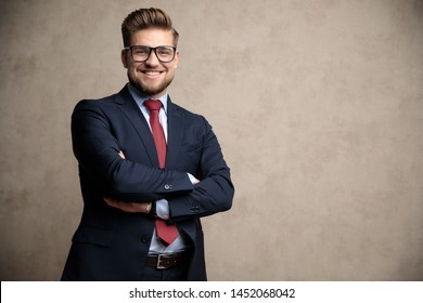 Jolly businessman smiling with his hand crossed at his chest while wearing a blue suit and glasses, standing on wallpaper background