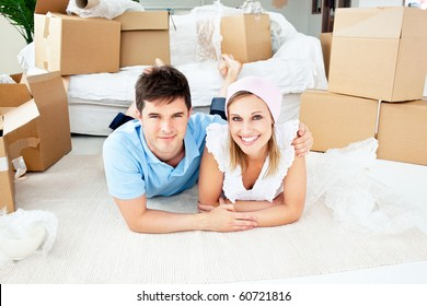 Jolly couple lying on the floor between boxes in their new house
