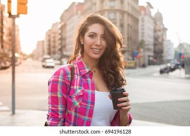 Jolly energetic woman holding take-away coffee