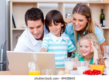 Jolly family using laptop during the breakfast in the kitchen