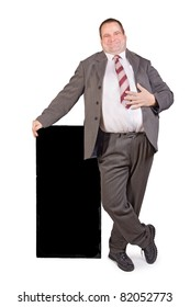 Jolly fat businessman standing on white background.Friendly fat man in a business suit stands at the black board. Obese businessman with a blank poster on a white background.