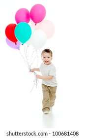 Jolly funny child boy with bunch of colourful balloons in his hand. Isolated on white.