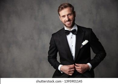 Jolly groom standing and fixing his black tuxedo while looking and smiling to the camera on gray studio background