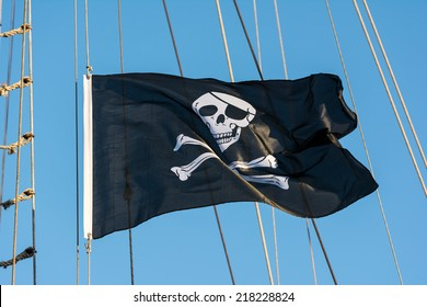 Jolly Roger Black Pirate Flag With Human Skull On Blue Sky