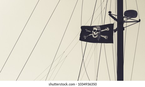 The jolly roger pirate flag flying high on a yacht