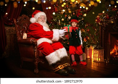 Jolly Santa Claus and his elf are preparing gifts for Christmas at home. Merry Christmas and Happy New Year!