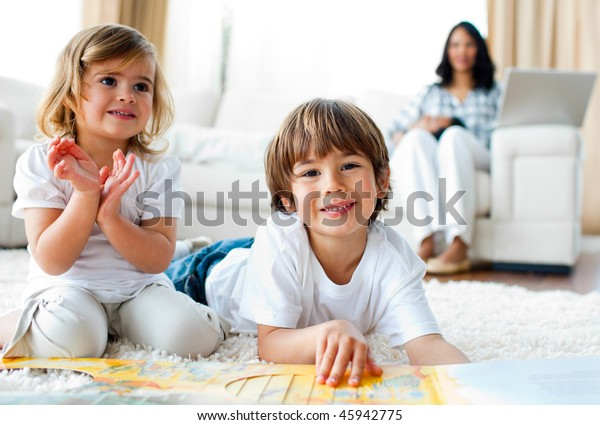 Jolly siblings eating chips and drawing lying on the floor