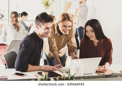Jolly smiling co-workers are sitting together near workplace and looking at screen of gadget