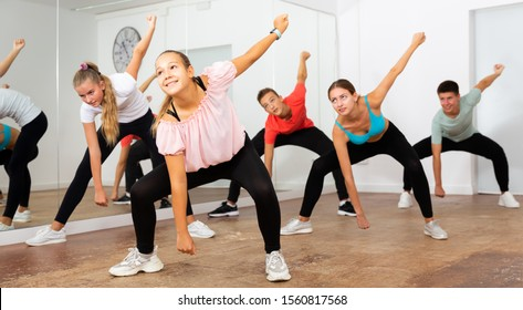 Jolly  teenage boys and girls dancing synchronous group choreography in dance hall