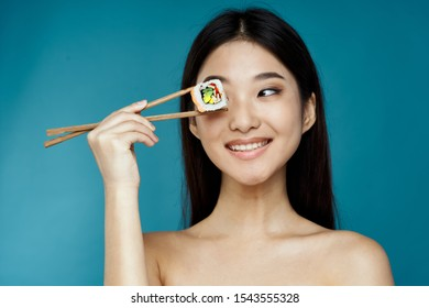 Jolly woman of Asian appearance fast food diet sushi chopsticks