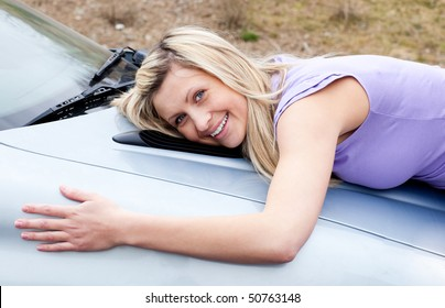 Jolly young female driver hugging her new car