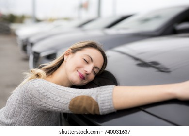 A Jolly young female driver hugging her new car