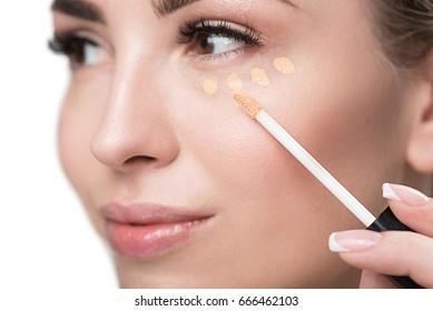 Jolly youthful woman using visage make-up