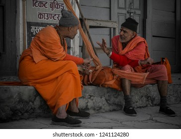 Jomsom, Nepal - May 12 2018: two monks dialogue at the bus stop on main street of Jomsom