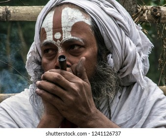 Jomsom, Nepal - May 12 2018: sadhu smokes chillum near the fence