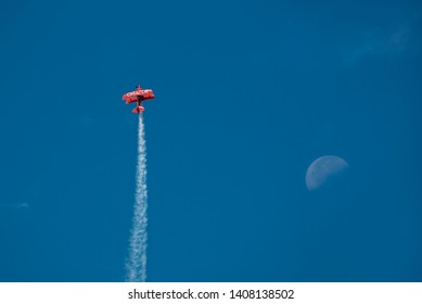 Jones Beach, New York, May 25, 2019: Jones Beach Air Show 2019. A red  Oracle plane is climbing high in the blue sky with a half moon.