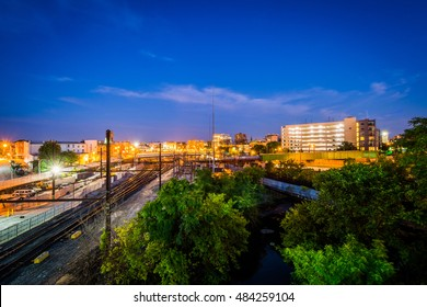 Jones Falls and a rail yard at night, seen from the Howard Street Bridge, in Baltimore, Maryland.