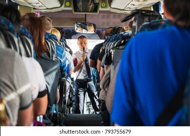 Jordan, Akaba - December 19, 2017: Tourists and a male tour guide with a microphone in the bus